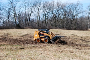Using the skid steer to ready the fields for spring planting